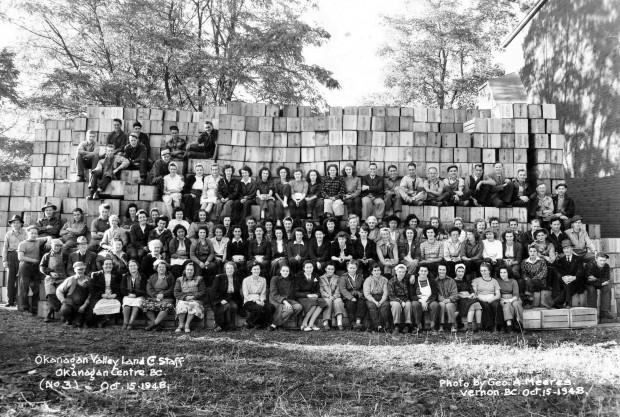 Photo officielle en noir et blanc représentant un grand groupe de femmes et d'hommes, à l'extérieur, sur des gradins, avec des caisses de pommes en arrière-plan.