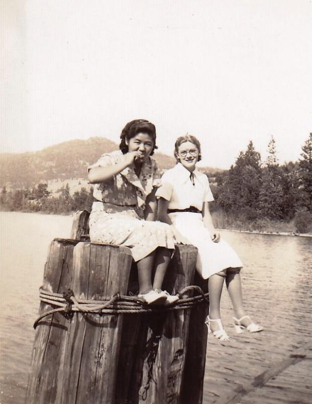 Photo en noir et blanc représentant deux jeunes femmes assises sur des pieux plantés dans un lac.