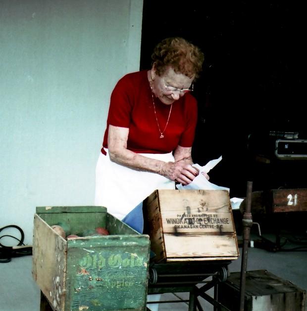 Photo en couleur d'une vieille femme debout sur une terrasse en train d'envelopper une pomme en bois avant de la déposer dans une des deux caisses de pommes placées devant elle. Elle a des cheveux roux frisés et porte un chandail rouge.