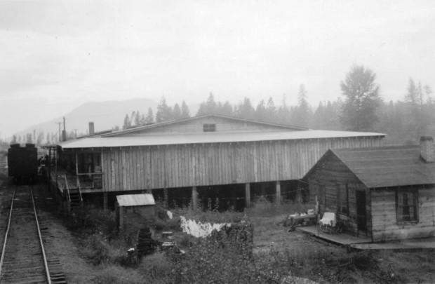 Photo en noir et blanc représentant une maison de bois avec du linge accroché devant. Près de la maison se trouve un vieil édifice assez grand en bois. Des rails de chemin de fer passent devant les deux bâtiments.