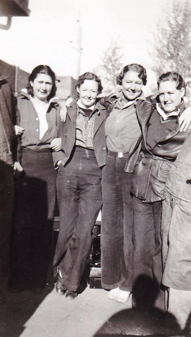 Photo en noir et blanc de quatre femmes debout, en extérieur. Elles portent des pantalons et se tiennent par les épaules.