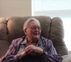 Photo en couleur d'une vieille femme aux cheveux blancs, portant des lunettes et assise sur un fauteuil; elle regarde vers la gauche en souriant. Elle porte un chemisier à rayures mauve.
