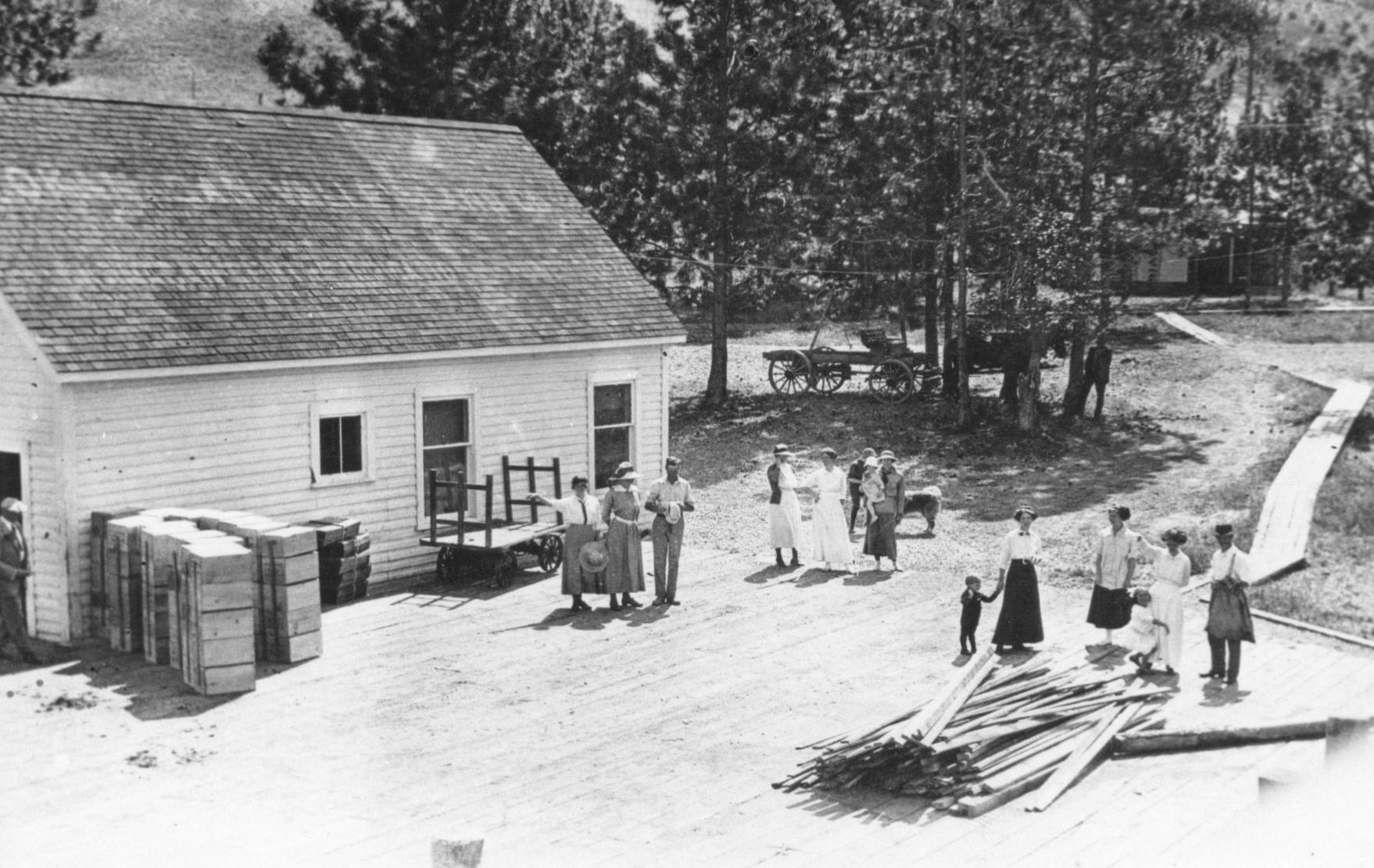 Photo en noir et blanc représentant plusieurs hommes, femmes et enfants sur une grande terrasse de bois devant un édifice blanc en bois; ils portent tous des vêtements du début du XXe siècle. Sur leur gauche, des piles de caisses de pommes et une charrette. En arrière-plan, des arbres, de l'herbe, un étroit trottoir en bois et une charrette attelée.