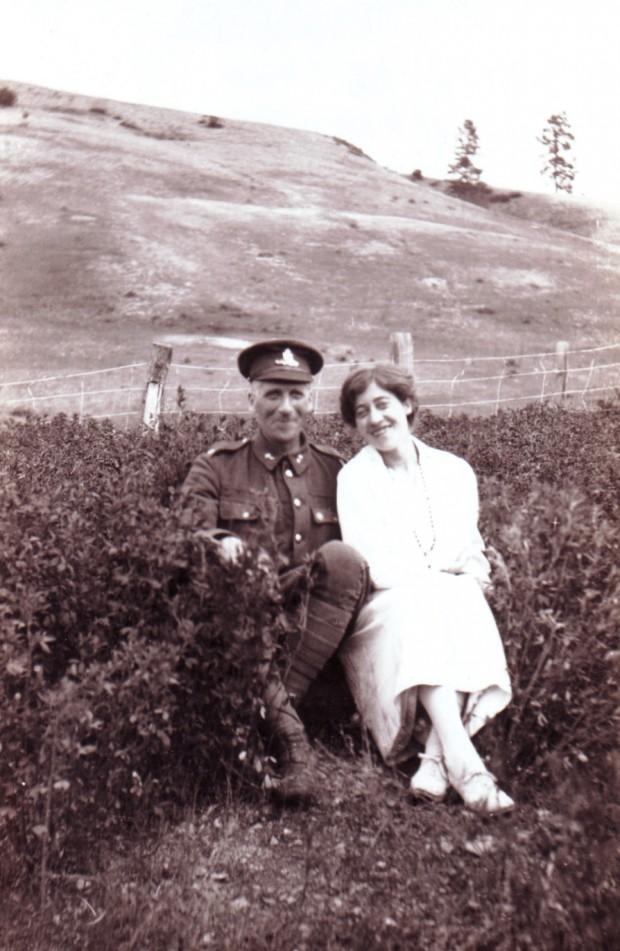 Photo en noir et blanc représentant un homme en uniforme militaire et une femme souriante assis dans un champ avec des collines en arrière-plan.