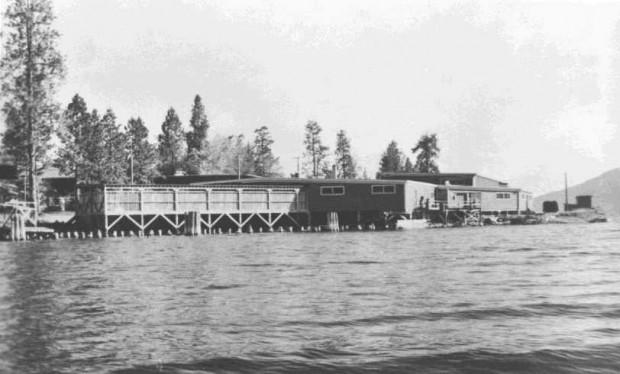Photo en noir et blanc représentant des édifices de bois sur la rive d'un lac. Une partie des bâtiments est construite sur pilotis au-dessus du lac.
