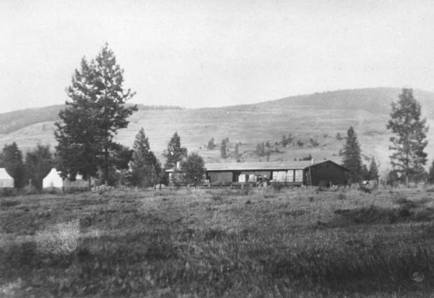 Photo en noir et blanc représentant un vieil édifice d'un étage dans un champ avec des collines en arrière-plan.