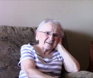 Photo en couleur d'une vieille femme aux cheveux blancs, portant des lunettes, assise sur un fauteuil. Elle sourit et a la tête posée sur sa main gauche.