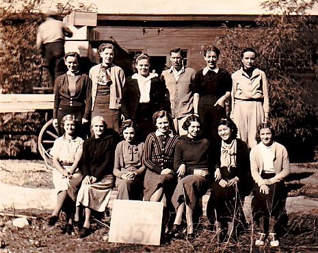 Photo sépia représentant douze femmes et un homme assis ou debout dehors. Derrière eux se dresse un vieil édifice de bois et l'on aperçoit un homme en train de décharger des caisses d'un wagon.