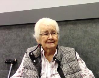 Photo en couleur d'une vieille femme portant une chemise blanche et des lunettes.