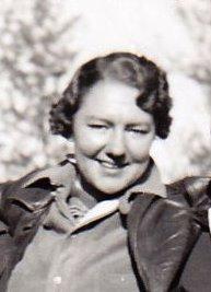 Photo en noir et blanc représentant une femme d'une trentaine d'années souriant au photographe.