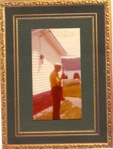 Le père John Hayes devant sa maison