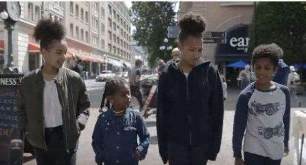 quatre jeunes, âgés de 6 à 15 ans, marchant côte à côte dans le square historique