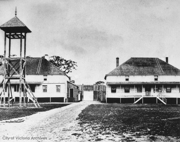 photo en noir et blanc, une tour d'observation se dresse devant deux grands bâtiments. Une porte située entre les deux s'ouvre sur un chemin passant entre les bâtiments