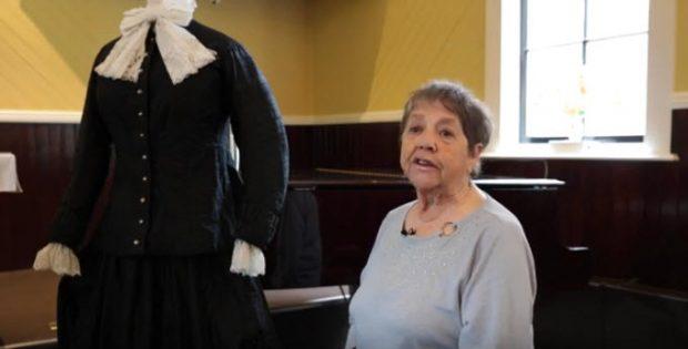 femme âgée assise sur un banc de piano dans une église, tournée vers la caméra; mannequin à sa droite arborant une longue robe noire de style colonial