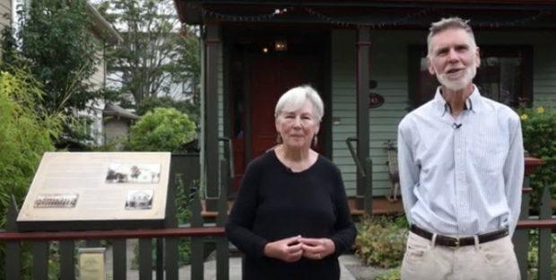 couple âgé sur le trottoir devant la maison. La femme a les mains croisées et l'homme a les mains derrière le dos