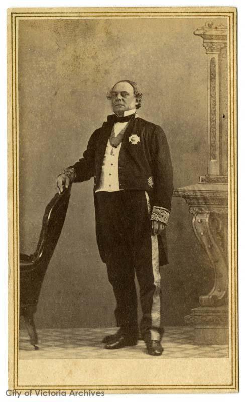 portrait professionnel officiel d'un homme âgé debout, vêtu d'un smoking avec col ailé et médaille au revers