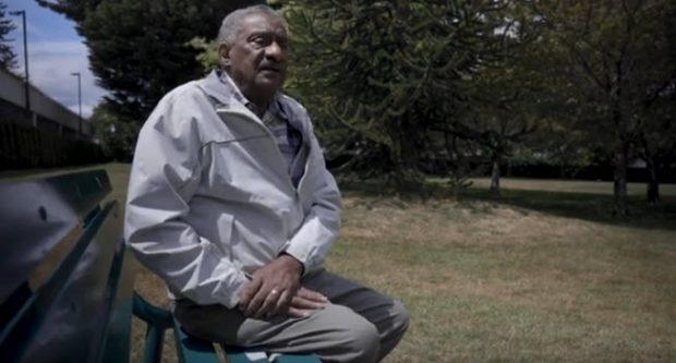 homme âgé, cheveux poivre et sel et moustache, assis sur un banc dans un parc gazonné, tournée vers la caméra. Arbres à feuilles persistantes en arrière-plan