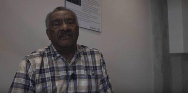 homme âgé, cheveux poivre et sel et moustache, assis dans la pièce. La plaque murale est partiellement visible au-dessus de son épaule droite