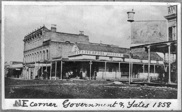 Le texte du bas indique « NE corner Government & Yates 1858 » (angle nord-est, rues Government et Yates, 1858). Intersection de deux rues en terre battue montrant des bâtiments commerciaux construits en bois et en brique de longueurs et hauteurs diverses avec différents types de toitures. On peut y voir quelques personnes et des chevaux