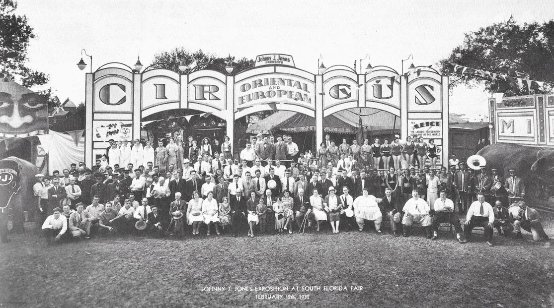 Une photo de groupe en noir et blanc d'un cirque, on peut y voir une femme très obèse, un groupe de musique, des gens en costume, des femmes en maillot de bain, au-dessus du groupe, il y a de grands panneaux sur lesquels le nom du cirque est écrit et un panneau représentant un visage peint avec une bouche ouverte