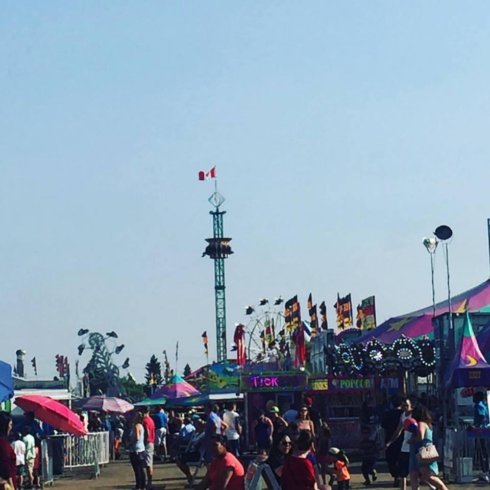 Les attractions d'une fête foraine comprenant des manèges et des stands, on voit un carrousel à l'avant, et en arrière-plan, les manèges Zipper, Super Hot et une grande roue