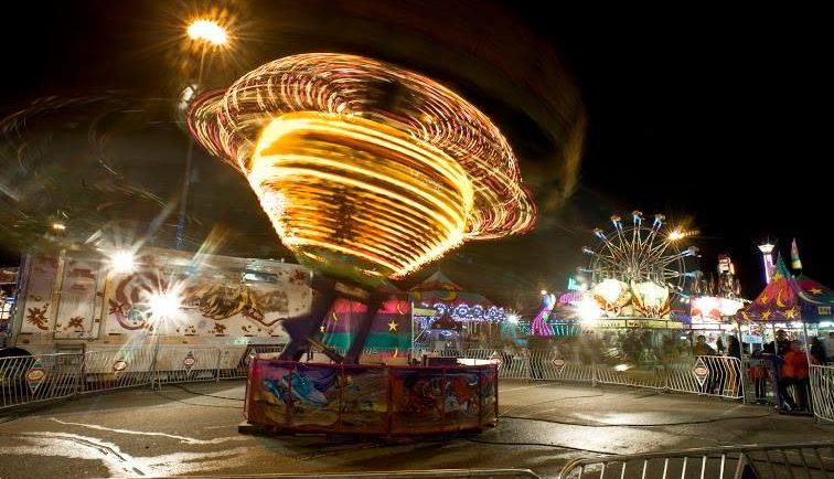 Dans une fête foraine, un manège illuminé tourne comme une toupie le soir et l'on voit une grande roue en arrière-plan