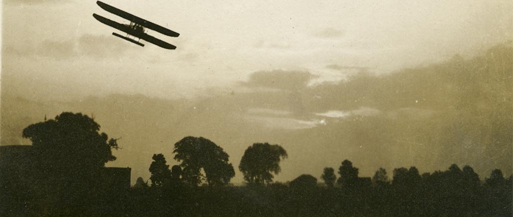 Un biplan vu à contre-jour au-dessus des arbres.