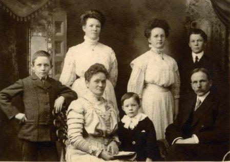 Une famille de sept personnes, élégamment vêtues.