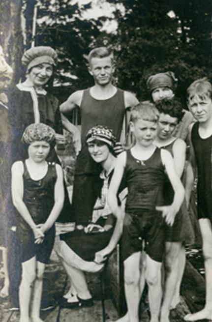 Un groupe composé surtout d'enfants en maillot de bain se tient sur un quai.