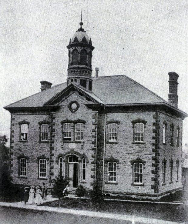 Grand bâtiment de deux étages, surmonté d'un clocher. Plusieurs femmes en robes longues en sortent par l'avant.