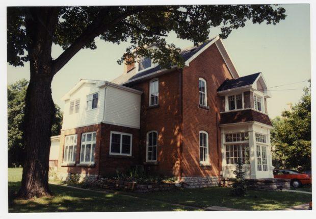 Grande maison de deux étages et demi en brique rouge, avec véranda vitrée.