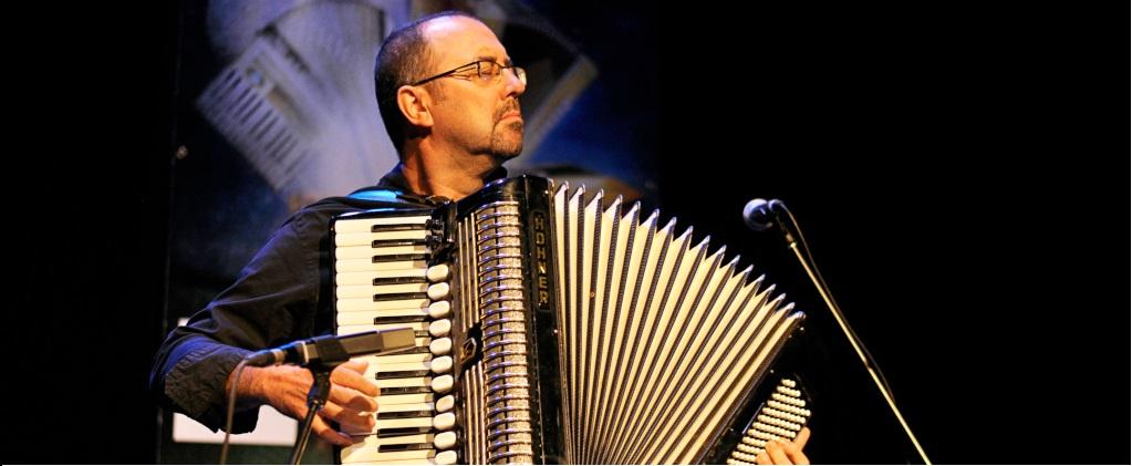 Photographie couleur où Martin Bellemare debout avec un accordéon-piano, les yeux fermés, joue face au public
