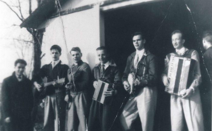 Photographie noir et blanc où sept hommes, composant un orchestre, pose devant une cabane à sucre.