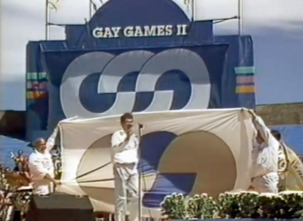 Lors des cérémonies de clôture des Gay Games II, Richard Dopson se tient sur la scène au micro devant un grand drapeau des Jeux gais tendu par la délégation de Vancouver.
