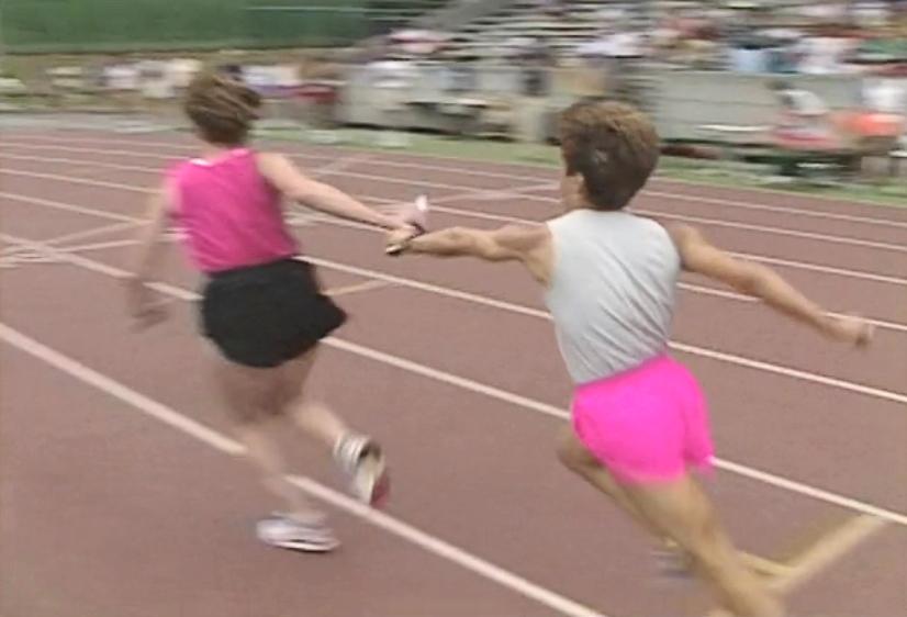 Deux femmes passent le relais au relais féminin au Swanguard Stadium de Burnaby.