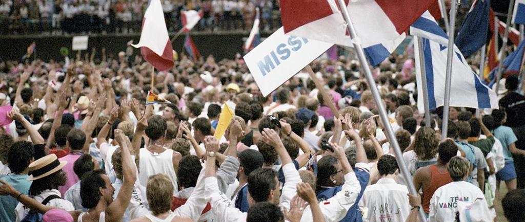 Des foules d'athlètes et d'autres participants, agitant divers drapeaux nationaux lors de la cérémonie d'ouverture de la célébration 90.