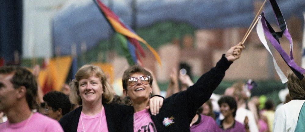 Un groupe d'athlètes féminines vêtues de t-shirts roses et de vestes noires sourit et salue la foule avec des banderoles colorées alors qu'elles marchent dans le défilé des athlètes lors des cérémonies d'ouverture. La gigantesque fresque de Vancouver qui soutenait la scène est visible en arrière-plan.