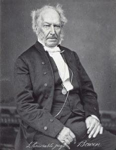 Photo noir et blanc. Un homme plus âgé en costume noir et une chemise blanche.