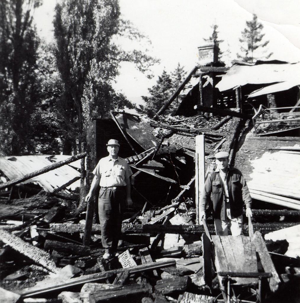 photo en noir et blanc d'un homme debout au milieu des décombres après un incendie