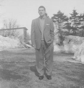 Photo grise d'un homme debout devant un bâtiment