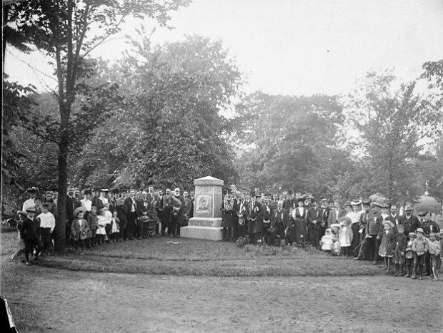 photo en noir et blanc d'un grand groupe de personnes autour d'un monument du cimetière pour une photo
