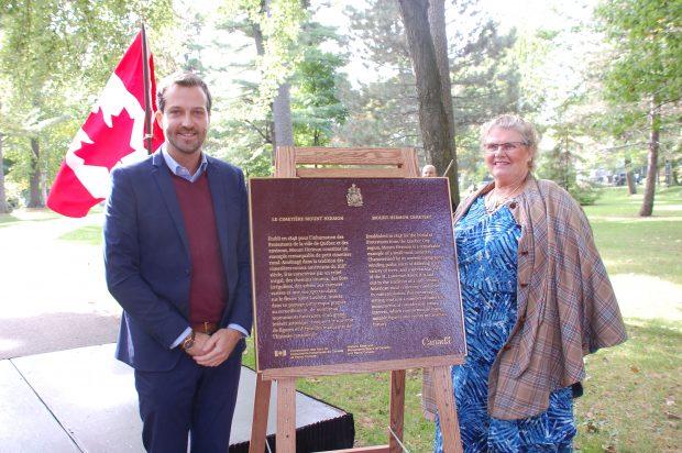 Homme et femme debout de part et d'autre d'une plaque commémorative du lieu historique national du Canada avec un drapeau canadien à l'arrière-plan