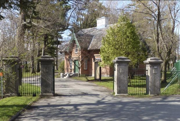 photo couleur d'une maison en briques entourée d'arbres et une clôture métallique avec une ouverture avec quatre grand poteau de ciment pour une belle allée.