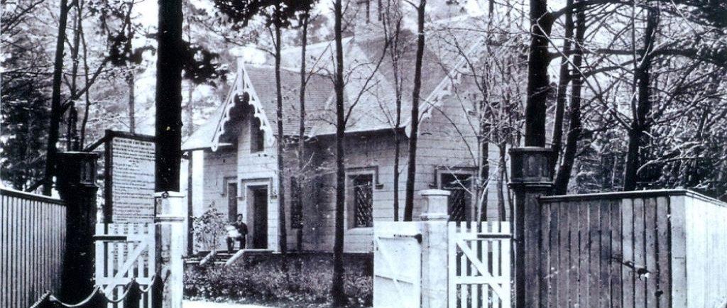 photo en noir et blanc d'une maison dans les bois. Un homme est assis sur l'étape avant la tenue d'un bébé vêtu blanc. Il y a aussi une grande clôture de bois devant la maison.