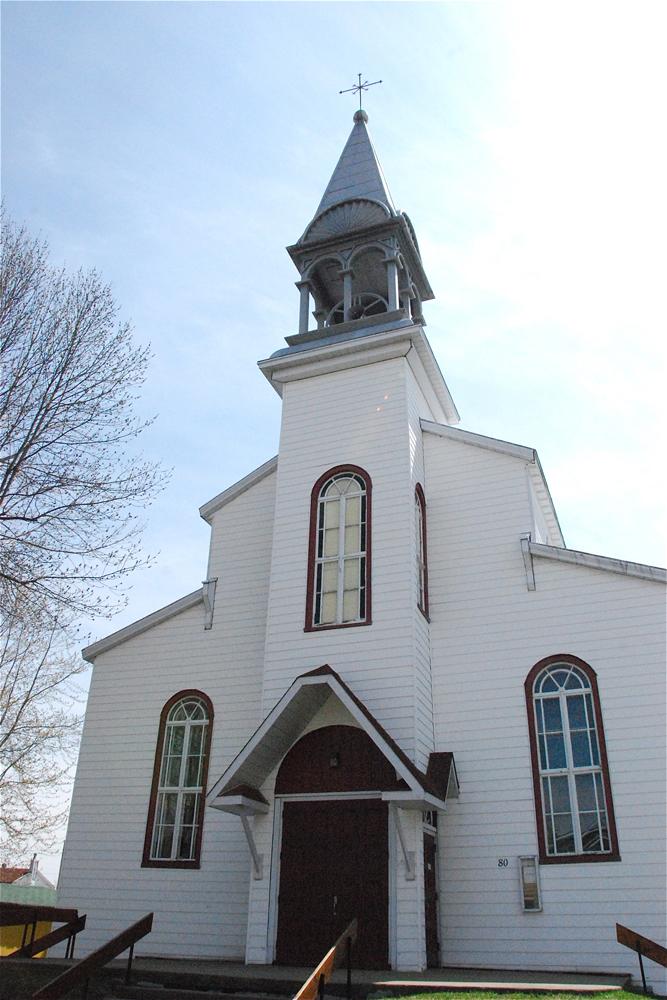 Photographie couleur, plan rapproché, façade d'une église en bois peint en blanc comprenant le clocher et le portique.