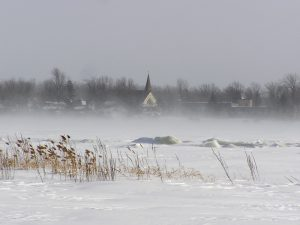 Color photograph taken in winter, long shot of a village on a frozen waterfront, in the center, a church steeple is visible through the low drifting snow.