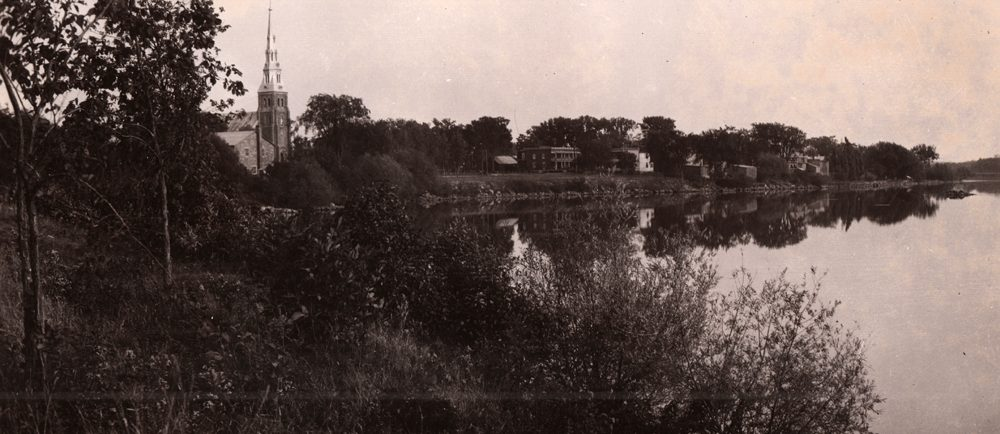 Photographie ancienne en noir et blanc, plan éloigné, en avant-plan, une vaste étendue d'eau, des arbres et de la végétation, en arrière-plan, le clocher d'une église avec à sa droite une série de petites maisons.