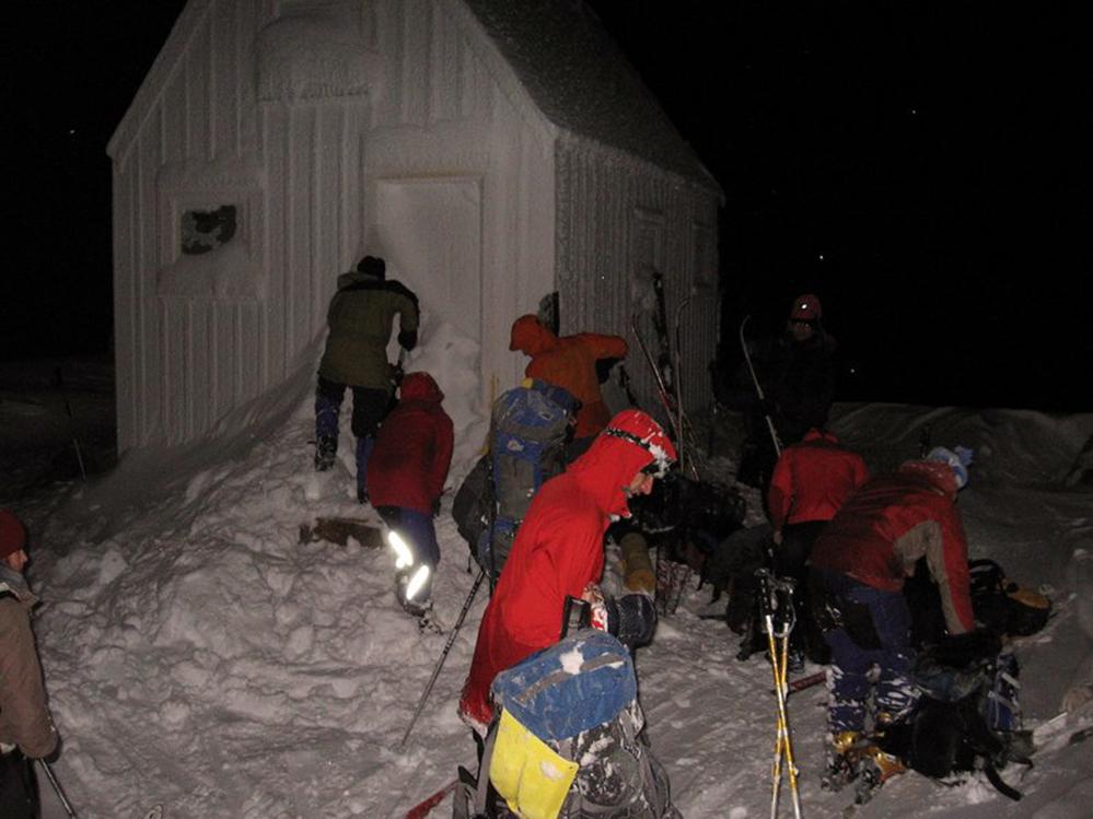 Trois membres déblayant la neige près de la porte principale. À leur extrême droite, un groupe de membres retirent leurs équipements de ski et rangent leurs effets.