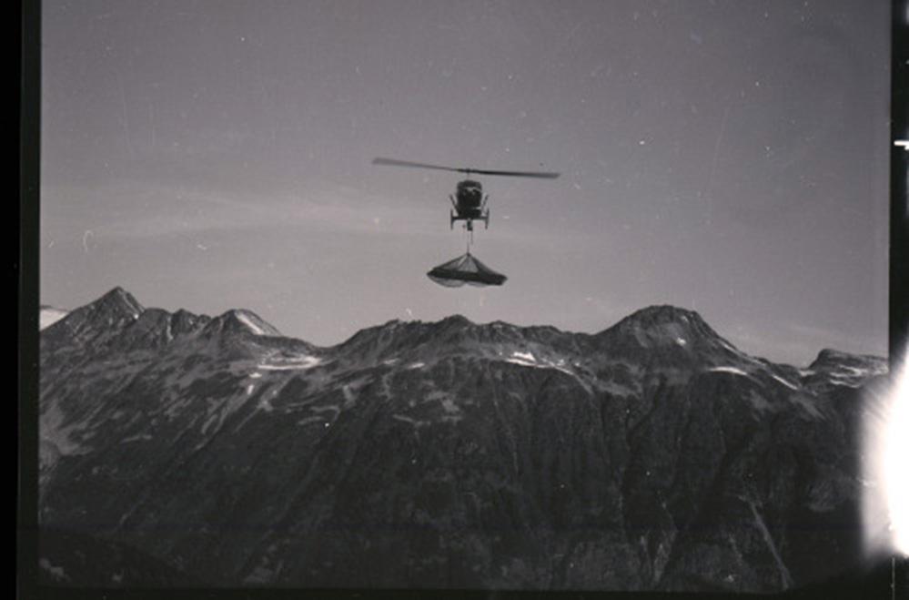 À l'arrière-plan se trouve une chaîne de montagnes avec de petits amas de neige. Au premier plan, l'hélicoptère transporte un chargement suspendu à un câble sous le cockpit.