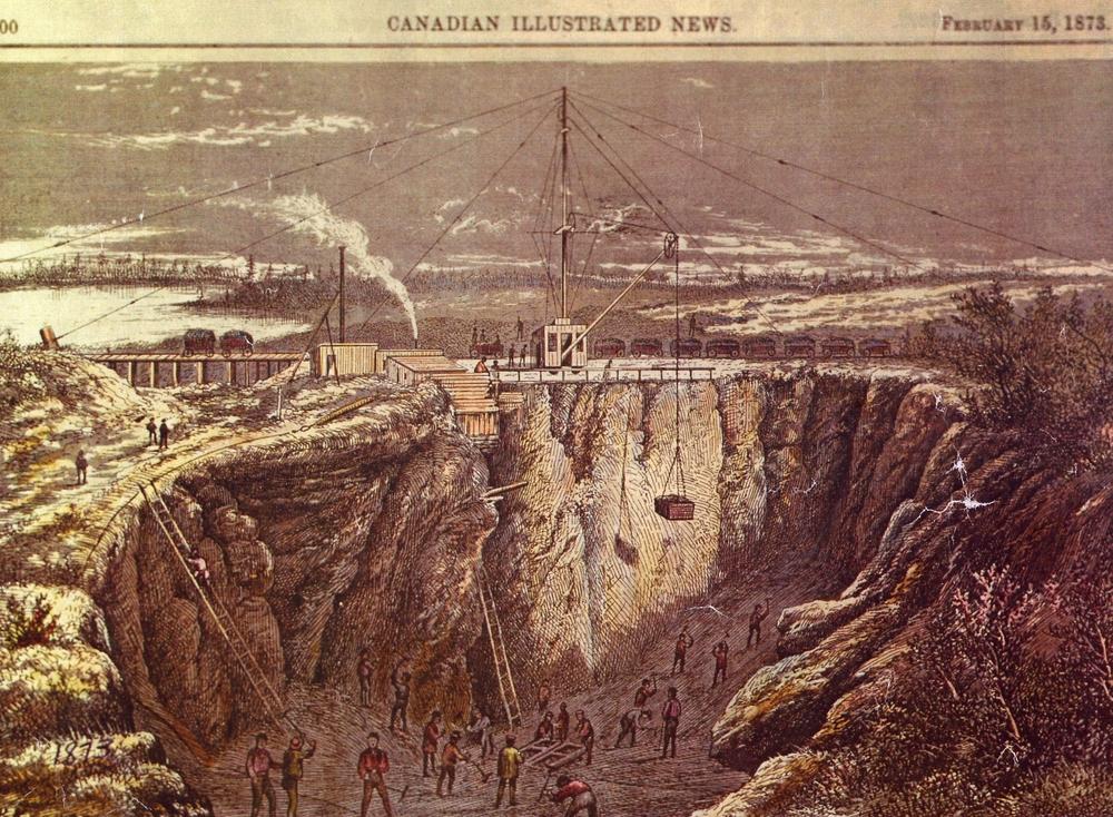 Une gravure à l'eau forte en couleurs du Canadian Illustrated News, datée du 15 février 1873, avec au moins 20 hommes qui effectuent diverses tâches dans une profonde mine à ciel ouvert. En haut de la mine, au centre de la gravure, il y a un grand chevalement maintenu par plusieurs câbles d'ancrage. Il y a aussi une rangée de wagons derrière le chevalement.